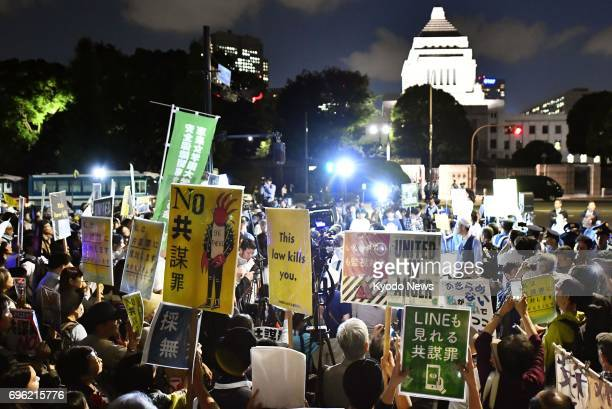 Protesters gather in front of the Diet building in Tokyo on the night of June 15 demonstrating against the ruling parties' steamrolling through the...