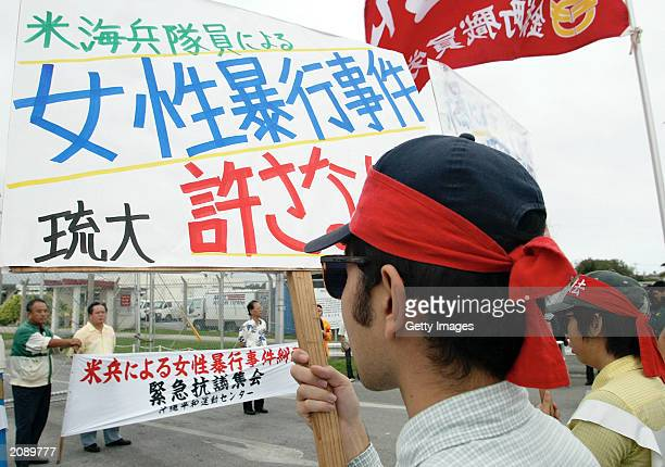 Protesters gather in front of the gate at the US military base Camp Hansen to protest the rape of a local woman in May allegedly by a US Marine June...