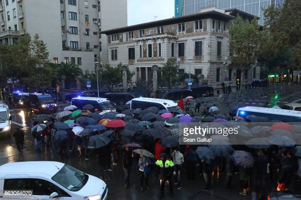 Protesters gather in pouring rain at the building that houses the representation of the Spanish government to demonstrate against the pending...