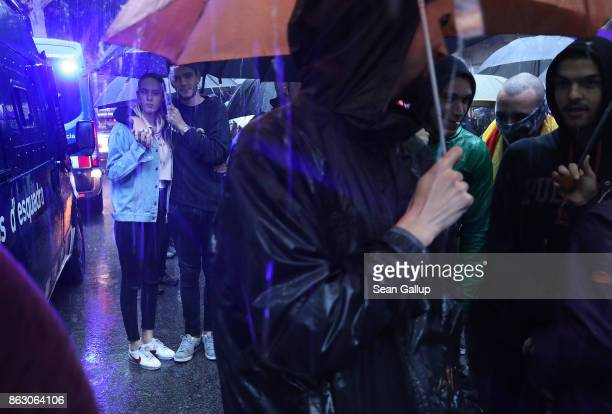 Protesters gather in pouring rain outside the building that houses the representation of the Spanish government to demonstrate against the pending...