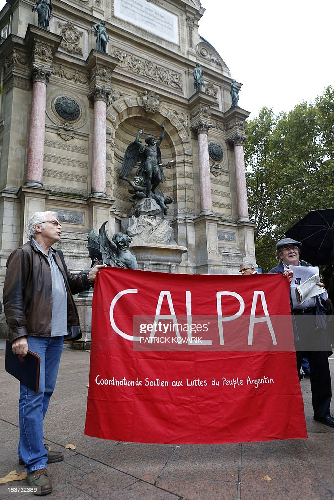 Protesters gather in support of the Argentine people on October 9, 2013 in Paris, as Franco-Argentinian former policeman Mario Alfredo Sandoval, suspected of crimes during the right-wing military regime that ruled Argentina from 1976 to 1983, is heard at a court in Paris for his extradition.