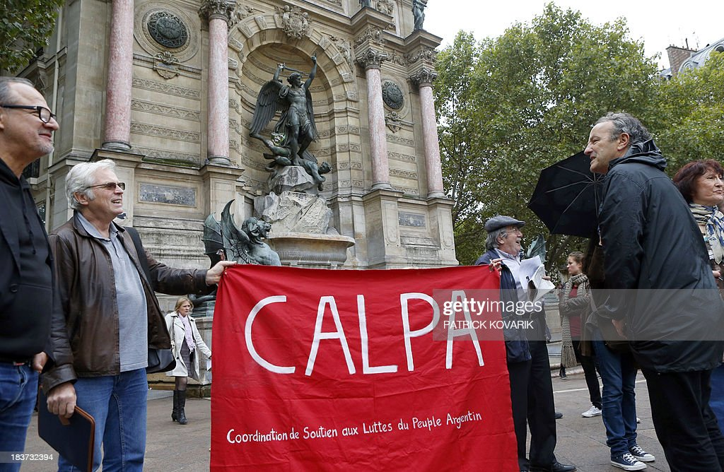 Protesters gather in support of the Argentine people on October 9, 2013 in Paris, as Franco-Argentinian former policeman Mario Alfredo Sandoval, suspected of crimes during the right-wing military regime that ruled Argentina from 1976 to 1983, is heard at a court in Paris for his extradition. AFP PHOTO / PATRICK KOVARIK