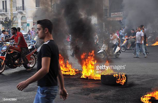 Protesters gather on motorbikes at a road block of burning tires in the northern Lebanese city for Tripoli on October 20 as they demonstrate against...