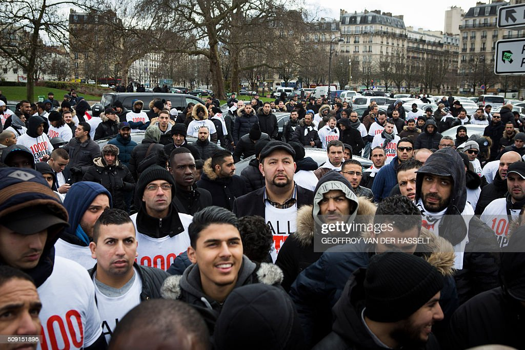 Protesters gather on the Place de la Nation in Paris on February 9, 2016, during a demonstration by non-licensed private hire cab drivers, known in France as VTC (voitures de tourisme avec chauffeur or tourism vehicles with chauffeur). VTC drivers continued a fifth day of protests on February 9 against measures granted by the French prime minister to taxi drivers. / AFP / Geoffroy Van der Hasselt