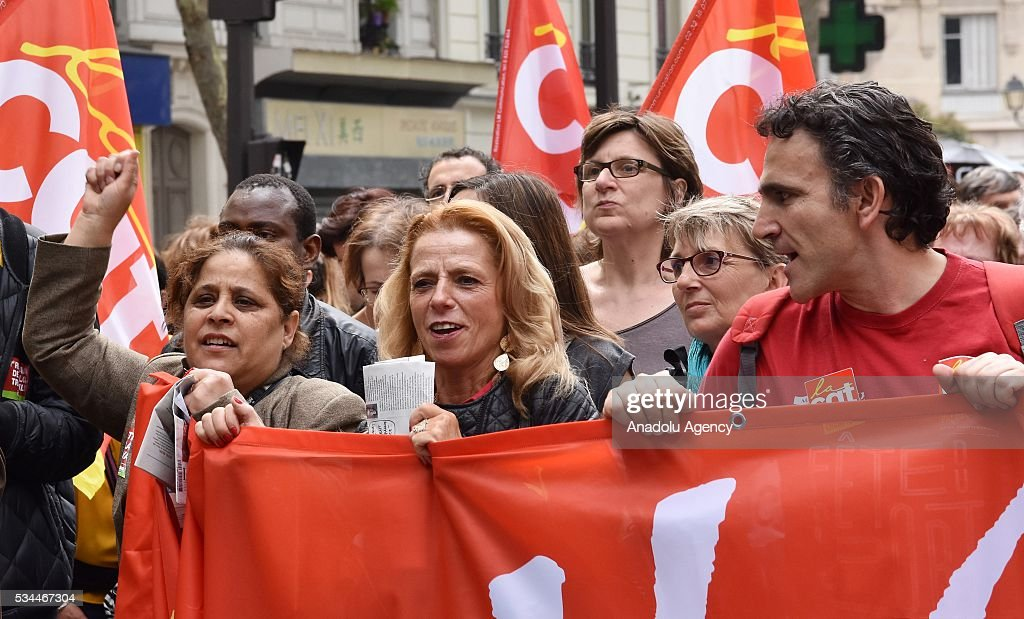 Protesters gesture and hold a banner as General Confederation of Labour (CGT) commences their 8th widespread protests all around the France for protesting French government's labor law reform in Paris, France on May 26, 2016.