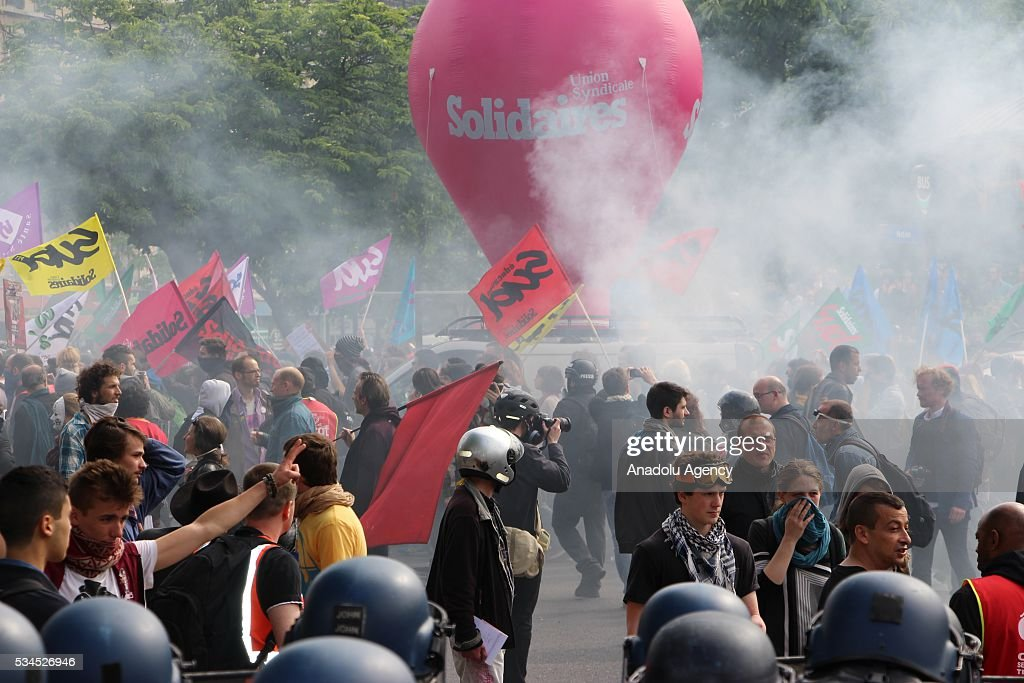 Protesters gesture and hold flags during the protests against French government's labor law reform in Paris, France on May 26, 2016.