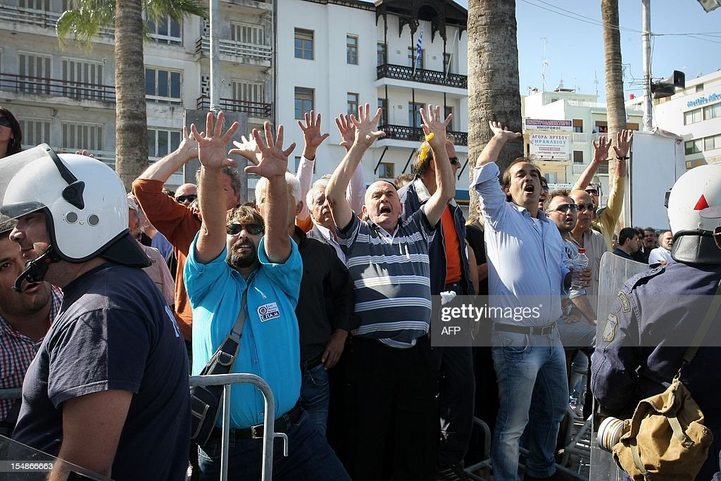 Protesters gesture at officials attending an annual student parade in Heraklion on the southern Greek island of Crete on October 28, 2012 during celebrations of the National No Day, commemorating Greece's refusal to surrended to Italian dictator Benito Mussolini's invading troops in 1940. AFP PHOTO/ Costas Metaxakis