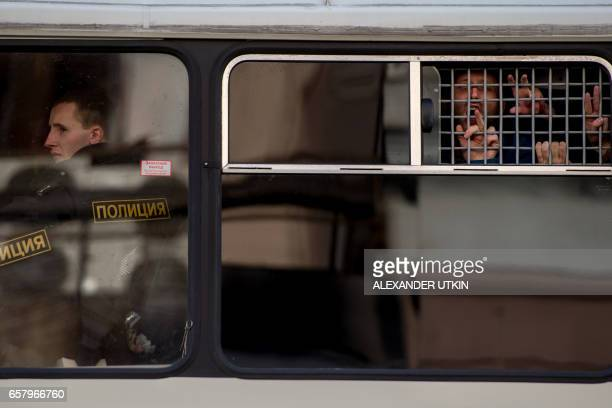 TOPSHOT Protesters gesture from a police bus after being detained during an unauthorised anticorruption rally in central Moscow on March 26 2017...