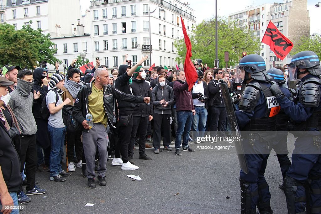 Protesters gesture next to French police during the protests against French government's labor law reform in Paris, France on May 26, 2016.