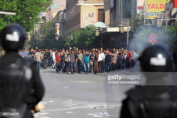 Protesters gesture towards security forces during clashes in Sulaimaniyah in Iraq's Kurdistan region on October 10 2015 Thousands of people took to...