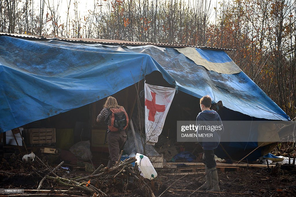 Protesters head towards a makeshift hospital after re-occupying a protected swampland on November 25, 2012 in Notre-Dame-des-Landes, near Nantes in western France, one day after squatters' eviction and clashes with anti-riot policemen. The airport, which is scheduled to replace the current airport at Nantes in 2017, is a pet project of Socialist Prime Minister Jean-Marc Ayrault, who was the city's mayor from 1989 until this year. AFP PHOTO DAMIEN MEYER