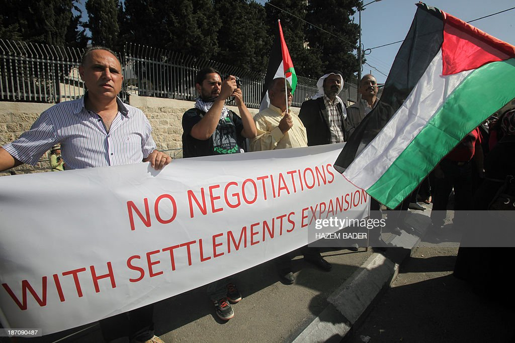 Protesters hold a banner denouncing the settlements expansion during a demonstration to protest against US Secretary of State's visit on November 6, 2013 in Bethlehem. Just before Kerry's arrival on November 5, a meeting between the negotiators in Jerusalem broke down over recent settlement moves, with Israel advancing plans for some 3,700 new settler homes in the past week alone.