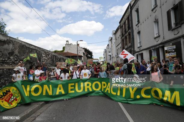 Protesters hold a banner during a demonstration against 'EuropaCity' a project of a giant commercial and leisure complex developed by Auchan retail...