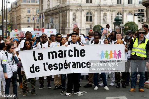 Protesters hold a banner reading '14th march of hope' to 'defeat autism' in Paris on April 1 2017 / AFP PHOTO / FRANCOIS GUILLOT