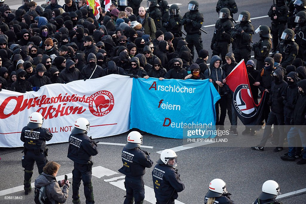 Protesters hold a banner reading 'Assholes party Germany' (Arschloecher feiern Deutschland) while taking part in a demonstration against a party congress of the German right wing party AfD (Alternative fuer Deutschland) at the Stuttgart Congress Centre ICS on April 30, 2016 in Stuttgart, southern Germany. Protesters tried to block the access to the party conference of the 'Alternative Fuer Deutschland' (Alternative for Germany) with around 400 being taken into custody. / AFP / Philipp GUELLAND