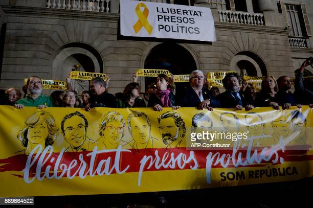 Protesters hold a banner reading 'Freedom to political prisoners' with portraits of detained officials Meritxell Borras Josep Rull Dolors Bassa...