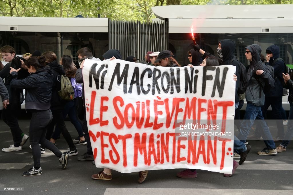 Protesters hold a banner reading 'Neither Macron nor FN, the uprising is now' during a demonstration against the results of the first round of the French presidential election in Nantes, western France, on April 27, 2017. Youths gathered to protest against far-right leader Marine Le Pen and former banker Emmanuel Macron, who both qualified on April 23 for the May 7 run-off in France's two-stage presidential election.