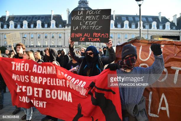 Protesters hold a banner reading 'Theo Adama and Babacar remind us why Zyed and Bouna were running' and a placard 'Police rapes lies kill The State...