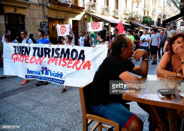 Protesters hold a banner reading 'Your tourism youth misery Living society' during a demonstration against mass tourism in the Spanish Basque city of...