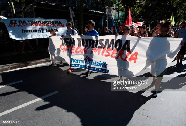 Protesters hold a banner reading 'Your tourism youth misery Living society' next to a banner reading 'It is not tourism phobia it is class warfare'...
