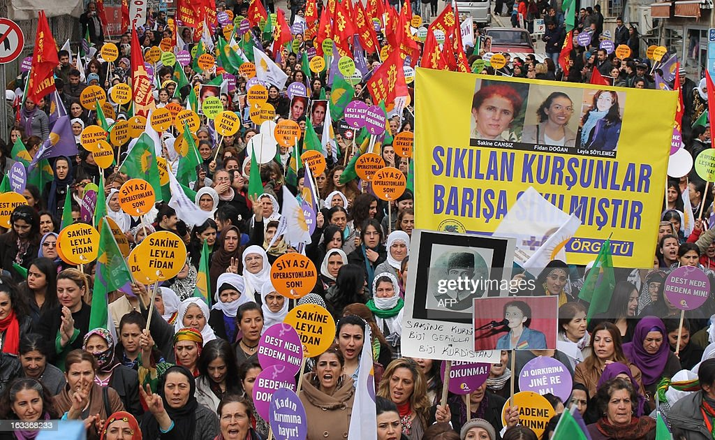 Protesters hold a banner showing the photographs of three Kurdish women activists murdered on January 9 in Paris, as they take part in a demonstration during the celebration of the International Women's Day on March 8, 2013, in Tunceli. The International Women's Day is marked on March 8 every year to pay tribute to women and their achievements.