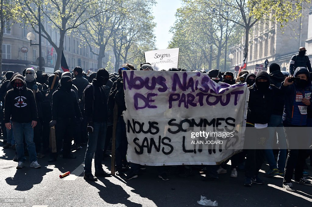 Protesters hold a banner that reads 'We are born everywhere - we are without limits' during a clash with French anti riot police during the traditional May Day demonstration in Paris on May 1, 2016.