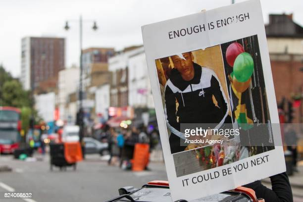 Protesters hold a banner with the image of 'Rashan Charles' reading 'Enough Is Enough It Could Be You Next' during a demonstration demanding justice...