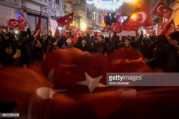 Protesters hold a large Turkish flag as they sing songs and chant slogans outside the Dutch Consulate on March 12 2017 in Istanbul Turkey Protesters...