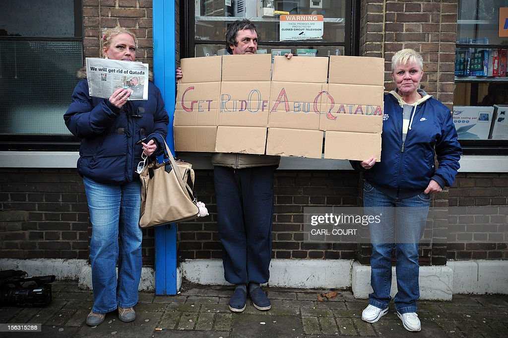 Protesters hold a placard against terror suspect Abu Qatada upon his arrival at his home in northwest London on November 13, 2012, after he was released from prison. Britain released the radical Islamist preacher from prison on bail after judges ruled that the man dubbed Osama bin Laden's right-hand man in Europe should not be extradited to Jordan.