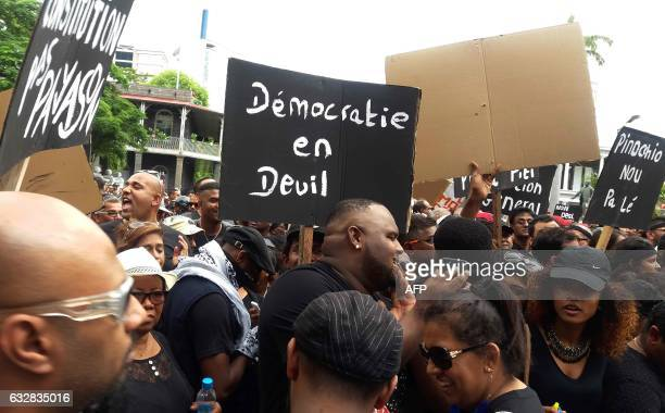 Protesters hold a placard reading 'Democracy in grief' during a demonstration in Port Louis on January 27 after former Prime Minister Sir Anerood...