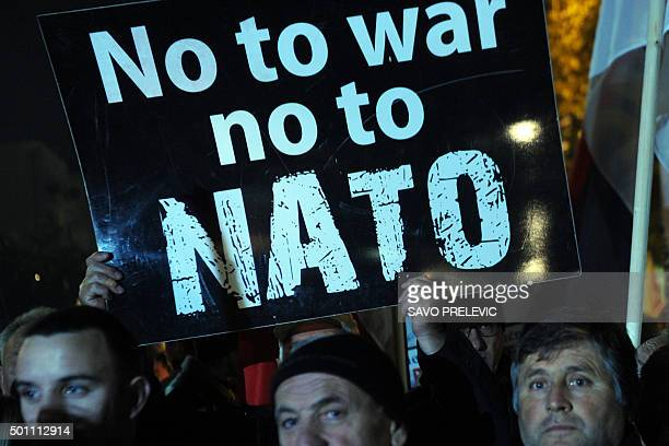 Protesters hold a placard reading 'No to war no to NATO' during a protest in Podgorica on December 12 2015 Several thousand supporters of proRussian...
