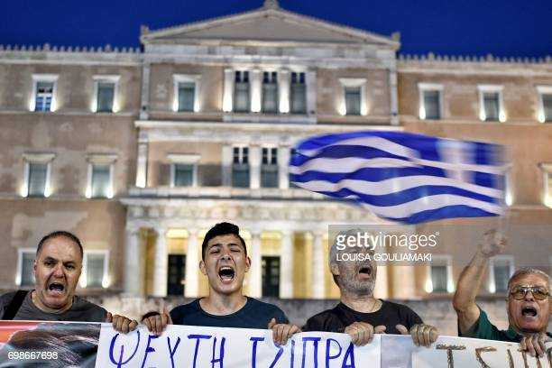 Protesters hold a placard reading ' Tsipras liar' as they chant slogans of 'resign' in front of the Greek Parliament in Athens on June 20 during a...