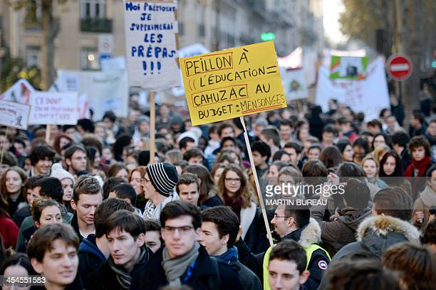 Protesters hold a sign reading 'Lies Peillon in education Cahuzac in the budget' as they march in Paris during a demonstration held by professors and...