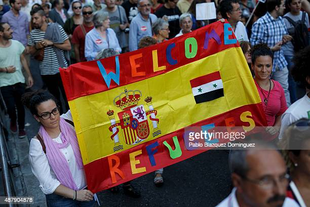 Protesters hold a Spanish flag reading 'Welcome refugees' during a demonstration to show solidarity and support for refugees on September 12 2015 in...
