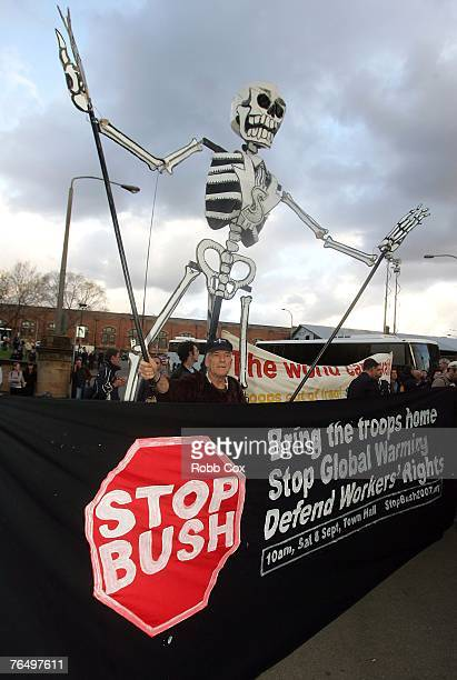 Protesters hold a Stop Bush sign as the figure of a skeleton dances behind during 'The Stop Bush Coalition' protest at the arrival of US President...