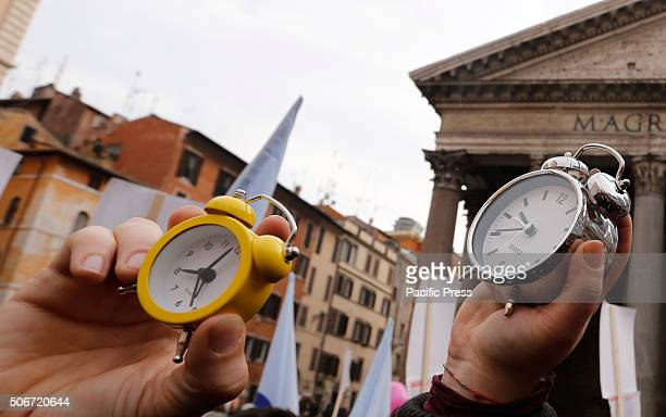 Protesters hold alarm clocks during demonstration in favor of civil unions rights including gay couples ahead of a parliamentary debate
