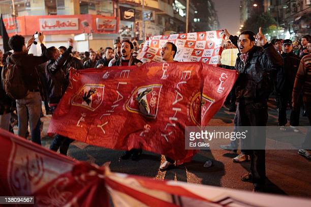 Protesters hold an Al Ahly football club flag during a march to the interior ministry after a demonstration outside Cairo's Al Ahly football stadium...