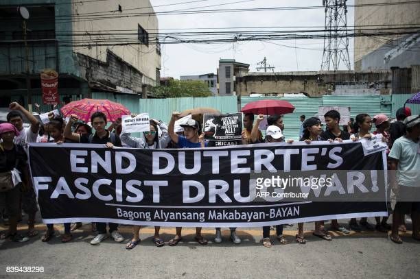 Protesters hold anti extrajudicial killing banners during the funeral march for 17yearold student Kian Delos Santos who was killed allegedly by...