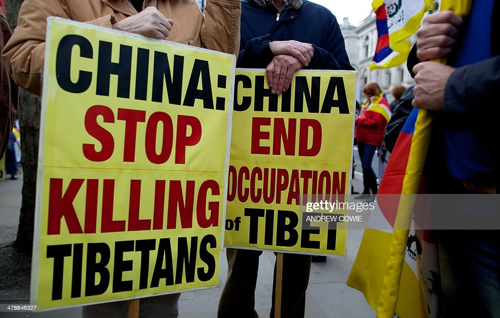 Protesters hold anti-China placards during a Free Tibet rally outside Downing Street in London on March 15, 2014. The annual march marks the anniversary of Tibetans' uprising against Chinese rule on March 10, 1959.