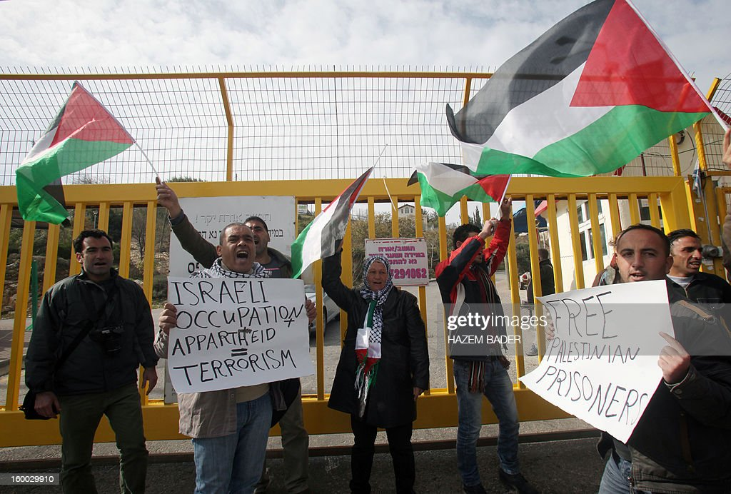 Protesters hold banners and Palestinian flags as they block the entrance of the El'azar Israeli settlement, south of the West Bank town of Bethlehem, to protest against the Israeli occupation and ask for the prisoners release on January 25, 2013.