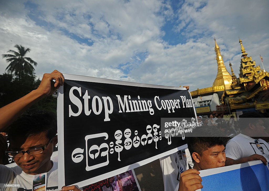 Protesters hold banners as they protest against Latpadaung copper mining plan in Yangon on November 26, 2012. The copper mine, a joint venture between military-owned Myanmar Economic Holdings and China's Wanbao company, has been the subject of controversy for months after local media allegations of corruption over the project. AFP PHOTO/ Soe Than WIN