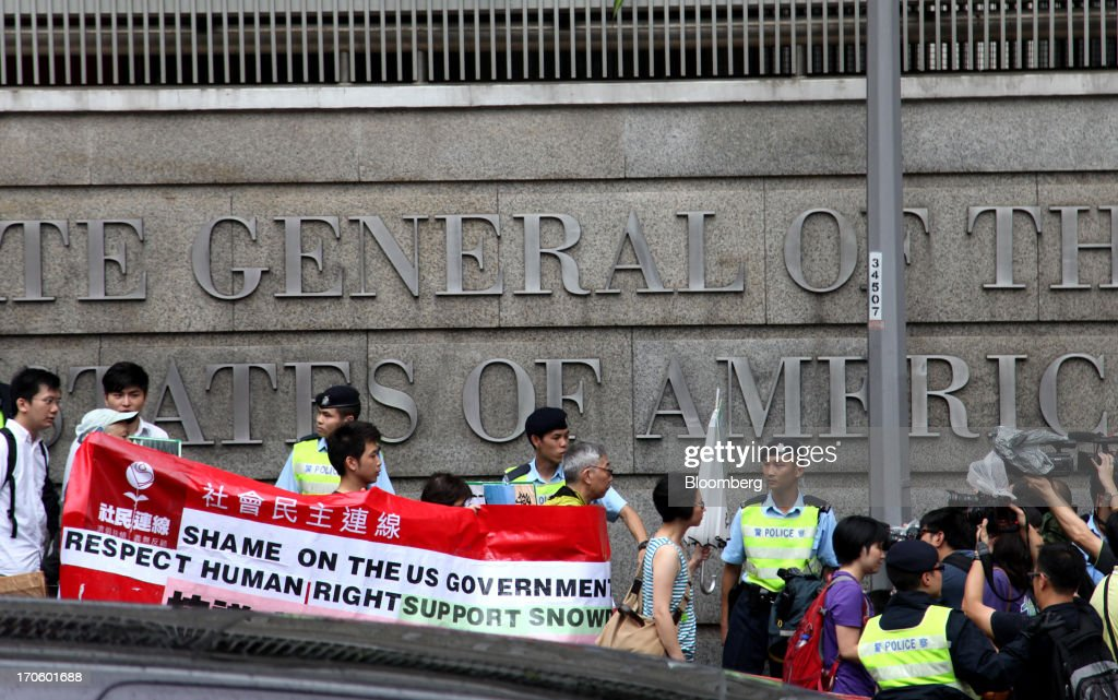 Protesters hold banners as they walk past the U.S. consulate during a rally in support of Edward Snowden, the former National Security Agency contractor, in Hong Kong, China, on Saturday, June 15, 2013. Protesters marched to Hong Kongs government headquarters demanding their leaders protect Edward Snowden, who fled to the city after exposing a U.S. surveillance program. Photographer: Luke Casey/Bloomberg via Getty Images