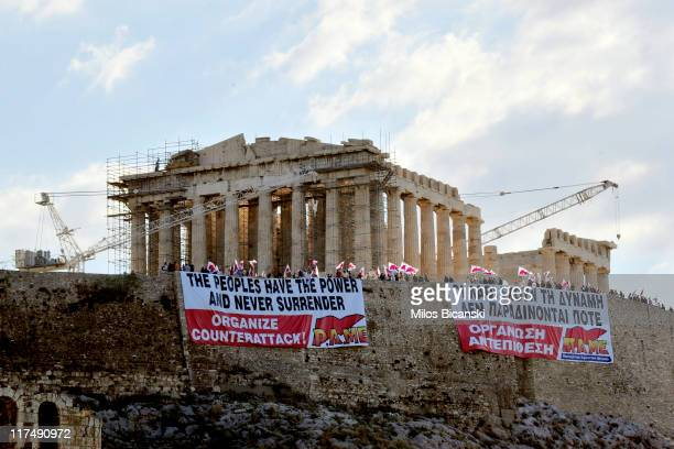 Protesters hold banners in front of the Parthenon on the Acropolis hill on June 27 2011 in Athens Greece Greek public and private sector labour...