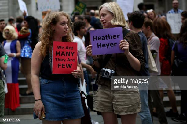 Protesters hold banners reading 'We Are Many They Are Few' and 'Heather Heyer' during a rally against US President Donald J Trump for threating North...