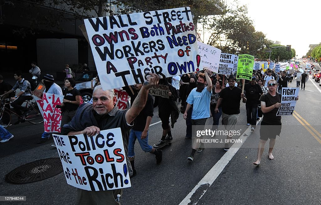 Protesters hold banners while shouting slogans during a late afternoon march through downtown Los Angeles on October 3, 2011 in solidarity with Occupy Wall Street protesters in New York City . They say they are inspired by revolutions in the Middle East, but protests over economic grievances in Spain and elsewhere in Europe are a closer comparison as anti-corporate demonstrations spread across the United States. As the Occupy Wall Street protest entered its third week Monday, it is being taken more seriously with similar sit-in demonstrations popping up from Boston to Chicago and Los Angeles and this week the New York protest expects to swell with support from trade unions. AFP PHOTO/Frederic J. BROWN