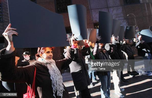 Protesters hold black posters symbolizing censorship while demonstrating against the proposed Stop Online Piracy Act and Protect IP Act outside the...