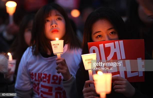 TOPSHOT Protesters hold candles and banners calling for the resignation of South Korea's President Park GeunHye during an antigovernment rally in...