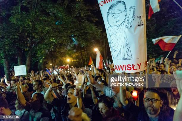 Protesters hold candles and shout slogans as they take part in a demonstration in front of the Polish Parliament as Polish Senators decide about new...