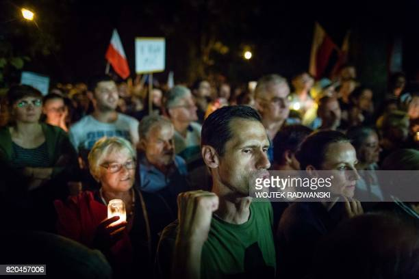 TOPSHOT Protesters hold candles and shout slogans during a demonstration outside the Polish Parliament as Polish Senators decide on a new bill...
