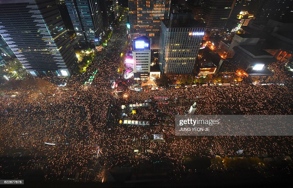 TOPSHOT - Protesters hold candles during an anti-government rally in central Seoul on November 12, 2016. Pressure on South Korea's scandal-hit president to resign escalated sharply on November 12, with organisers claiming a million-strong turnout at one of the largest -- and loudest -- anti-government protests the country has ever witnessed. / AFP / JUNG